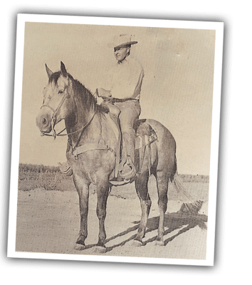John Ewing riding a horse in a black and white